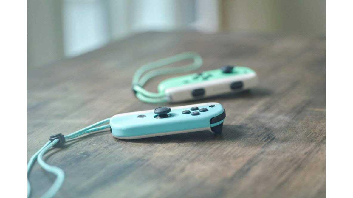 קונסולת Nintendo Switch במהדורת אנימל קרוסינג - בקרי ג'וי-קון על שולחן עץ