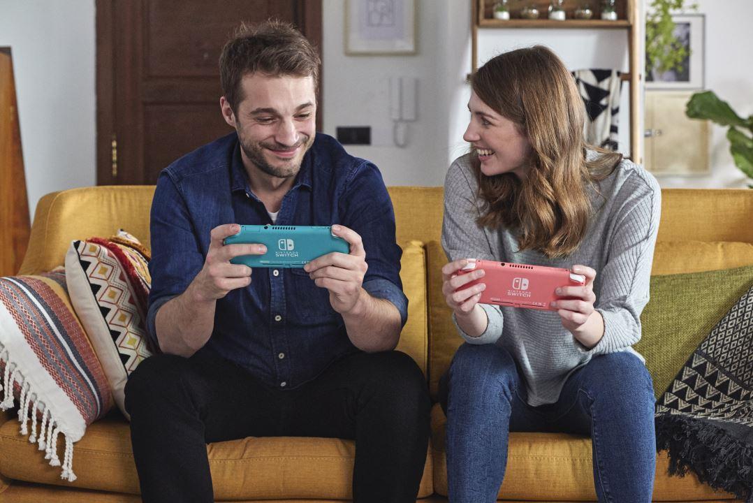 זוג צעיר משחק בנינטנדו סוויץ' בצבעים ורוד וטורקיז